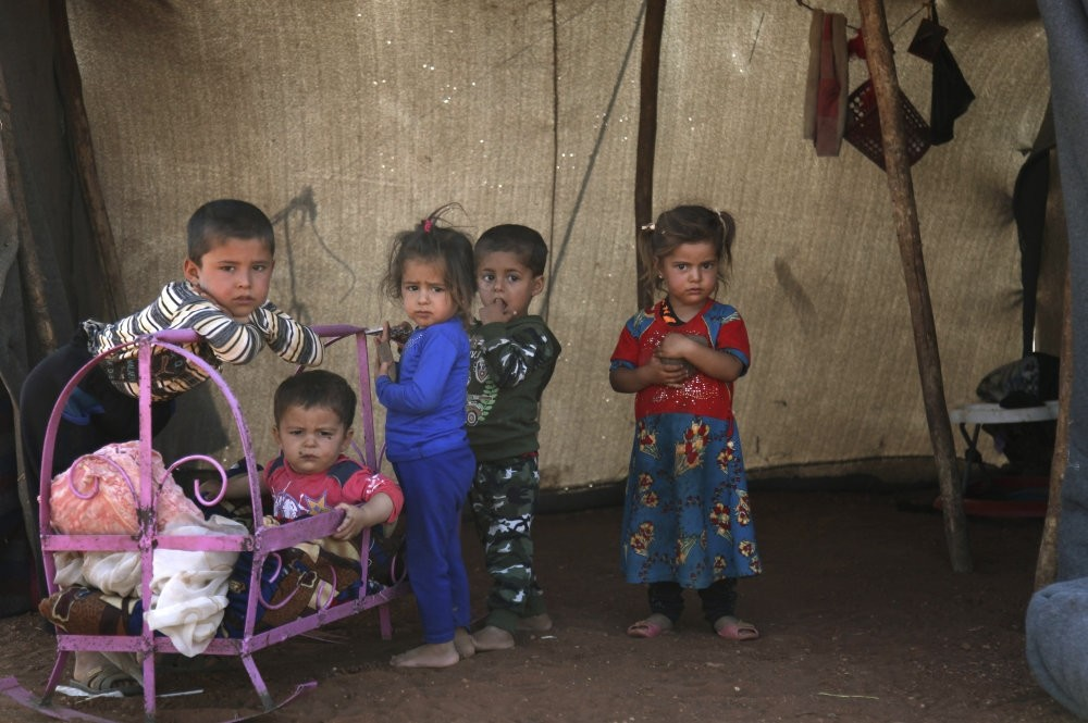 Syrian children stand outside of a tent in Idlib.