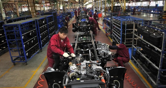 Workers install the chassis along a production line at a truck factory in Hefei, Anhui province, China.