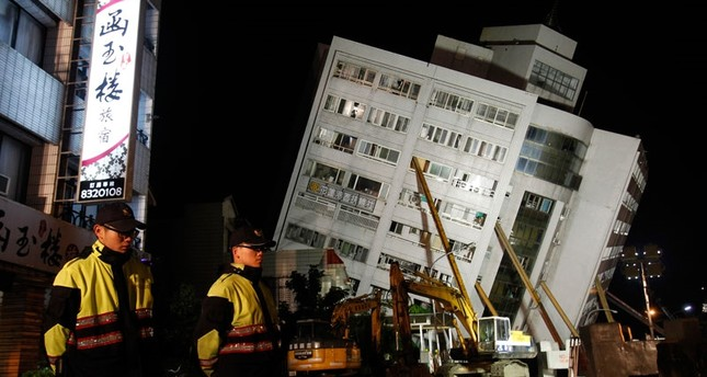 Two police officers guard outside of a collapsed apartment building in Hualien County, eastern Taiwan, Wednesday, Feb. 7 2018. A strong earthquake struck eastern Taiwan late Tuesday night. (AP Photo)