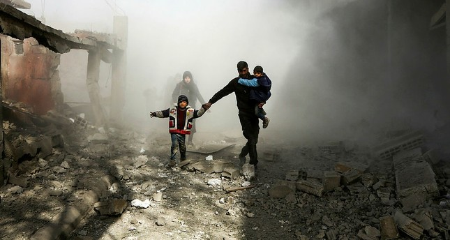 Syrian civilians flee from reported regime airstrikes in the besieged Eastern Ghouta region on the outskirts of the capital Damascus, Feb. 8.