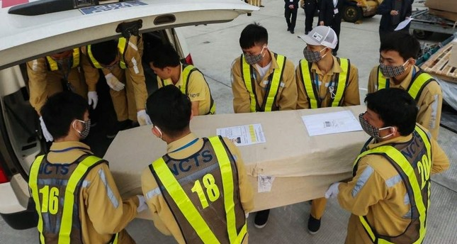 Photo taken on Nov. 27, 2019, shows ground personnel of Noi Bai International Airport carrying a casket containing the remains of one of the Vietnamese victims to an ambulance in Hanoi. (VIETNMA NEWS AGENCY via AFP)