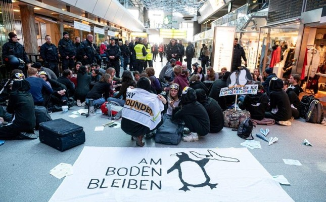 Climate activists block the entrance hall of Tegel Airport in Berlin, Germany, Sunday, Nov. 10, 2019. (AP Photo)