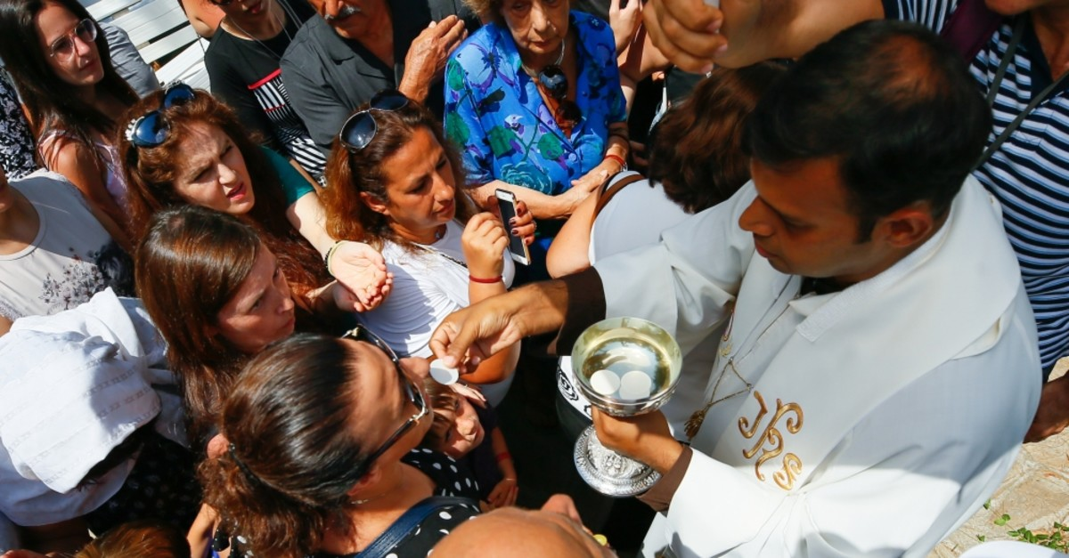 A priest delivering wafers to the faithful at the religious service outside the House of Virgin Mary in u0130zmir, Aug. 15, 2019.