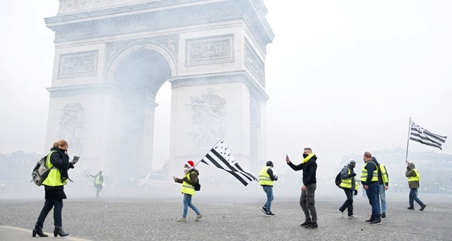 Tear gas floats in the air near the Arc de Triomphe as protesters wearing yellow vests, a symbol of a French drivers' gather to protest against higher diesel taxes, demonstrate in Paris, France, December 1, 2018. (REUTERS Photo)