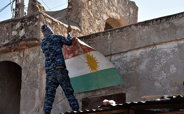 An Iraqi soldier removes a KRG flag from Altun Kupri on the outskirts of Irbil, Iraq, Oct. 20.