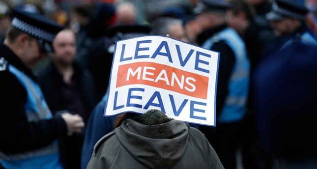 A pro-leave supporter carries a placard during demonstrations in London, Tuesday, Jan. 29, 2019. (AP Photo)