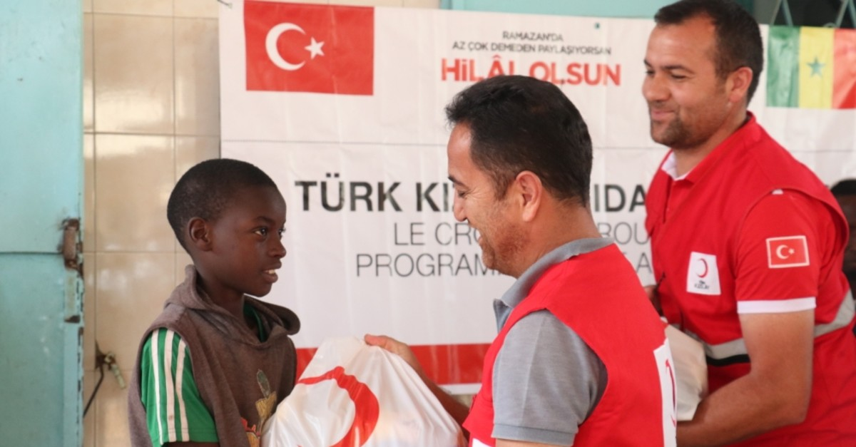 Red Crescent workers give a food package to a boy in Senegal's Dakar, May 31, 2019.