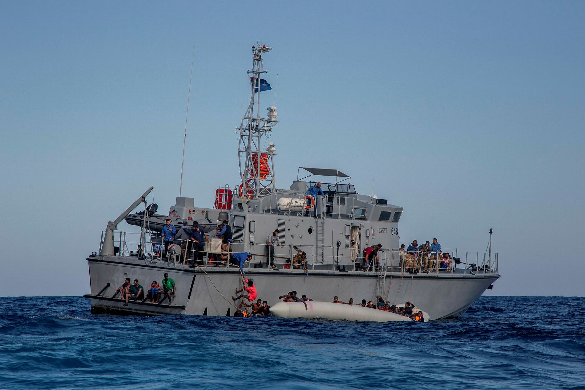 The Libyan coast guard tries to recover migrants from a rubber raft on the Mediterranean Sea, Nov. 6.