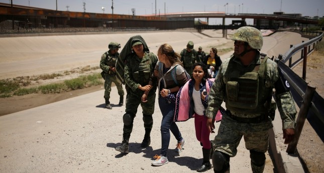 Members of Mexico's National Guard escort a woman and her daughter from Nicaragua after detaining them as they were trying to cross illegally the border between the U.S. and Mexico, in Ciudad Juarez, Mexico June 21, 2019. (REUTERS Photo)