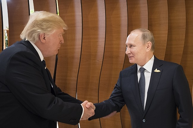 In this photo provided by German government U.S. President Donald Trump (L) shakes hand with Russian President Vladimir Putin before the first working session of the G-20 summit in Hamburg, northern Germany. (Presse- und Information via AP)