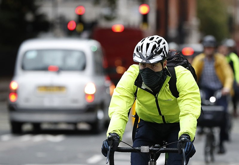 A cyclist wears a mask in central London, Monday, Oct. 23, 2017. The Mayor of London Sadiq Khan officially launched T-Charge on Monday. (AP Photo)