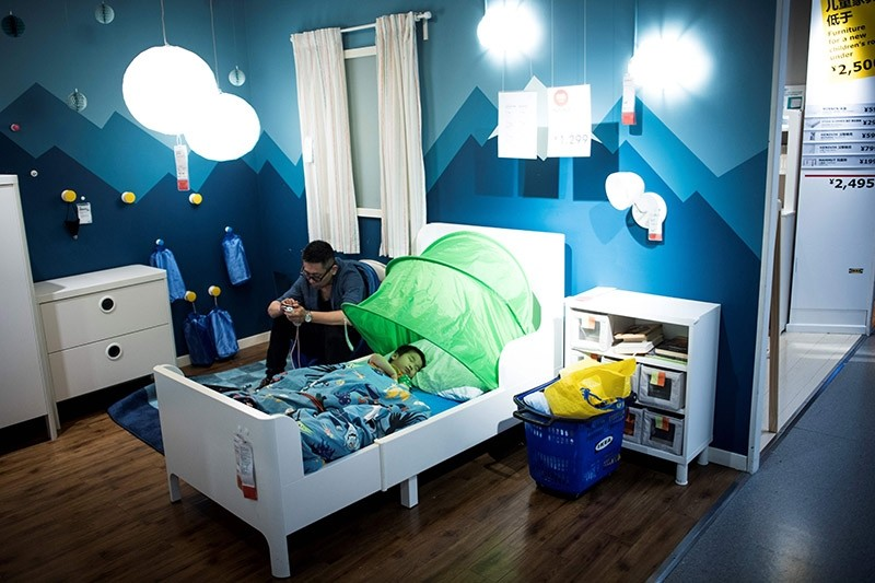 This picture taken on July 5, 2017 shows a father with his child escaping the summer heat by letting him sleepn in a bed in a Ikea store in downtown Shanghai. (AFP Photo)