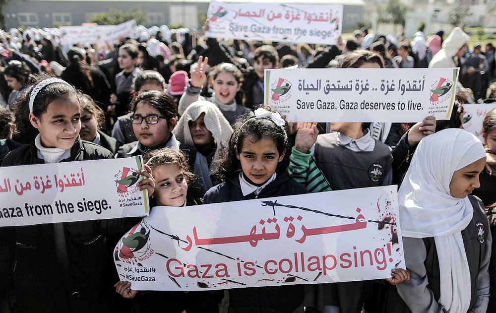 Palestinian schoolchildren shout slogans and hold placards during a protest in Gaza city on February 4, 2018, against the US decision to withhold funds earmarked for the UN relief agency for Palestinian refugees, UNRWA. (AFP PHOTO)