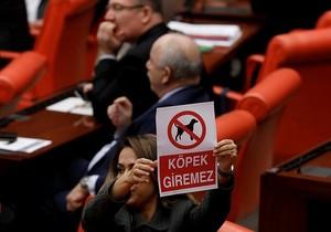 AK Party deputy Gökcen Özdoğan Enç shows a banner that reads 'no gods allowed.'
