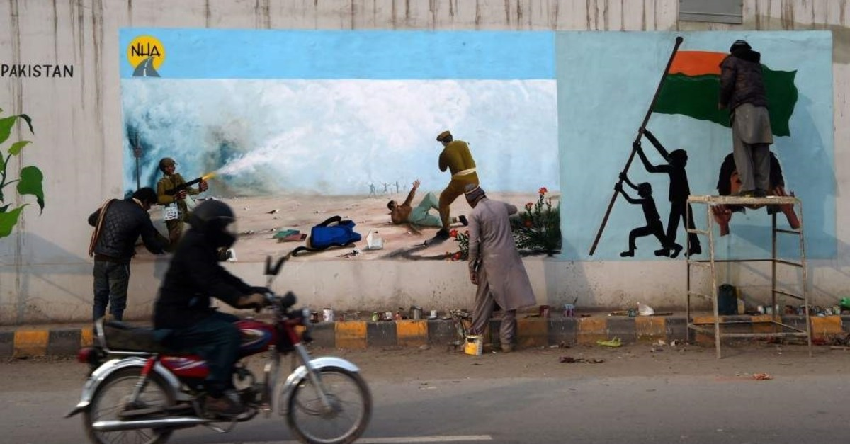 Artists paint graffiti on a bridge wall to show their solidarity with Indian Kashmiri Muslims, Peshawar, Feb. 4, 2020. (AFP Photo)
