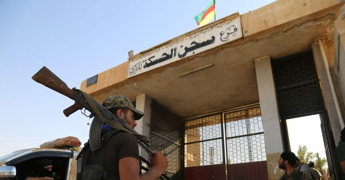 YPG terrorists stand outside the central prison of the northeastern Syrian city of Hasakeh on Aug. 23, 2016 after they agreed to a truce with regime forces (AFP File Photo)