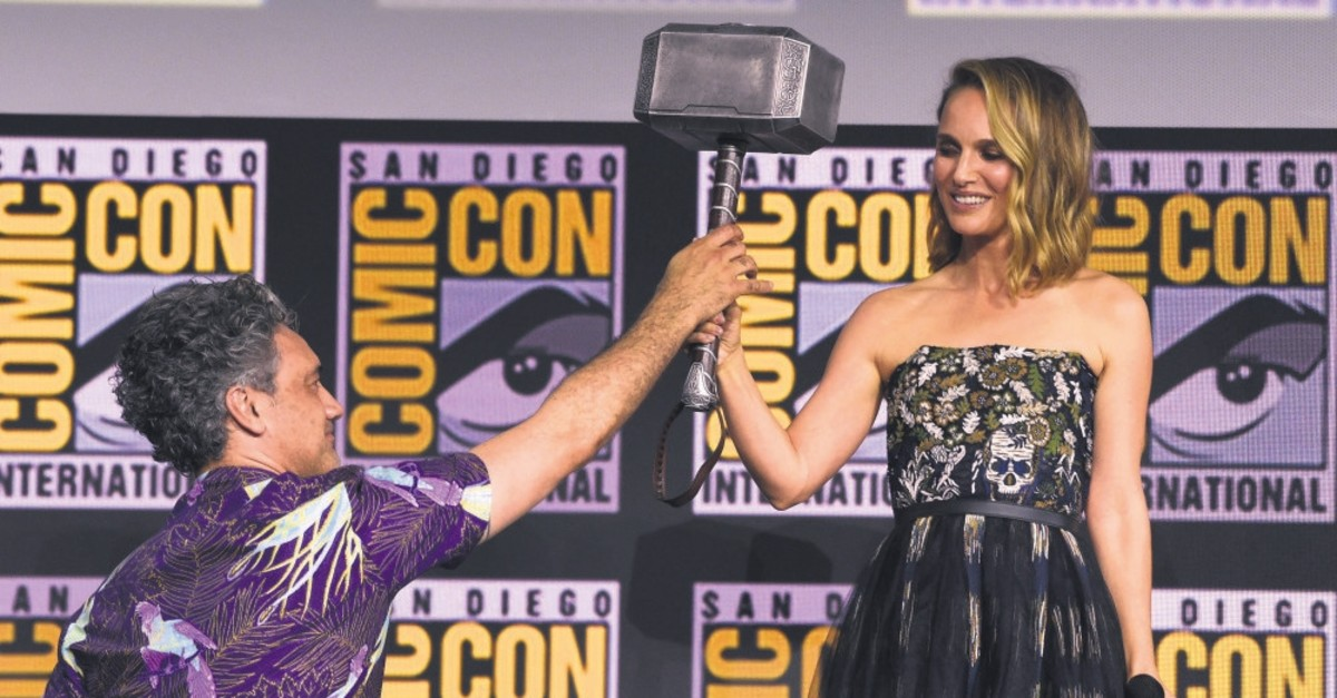 Director Taika Waititi hands the Thor hammer to Natalie Portman during the ,Thor Love And Thunder, portion of the Marvel Studios panel on day three of Comic-Con International on July 20, 2019, in San Diego.