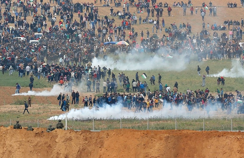 A picture taken on March 30, 2018 from the southern Israeli kibbutz of Nahal Oz across the border from the Gaza strip shows tear gas grenades falling during a Palestinian tent city protest commemorating Land Day. (AFP Photo)