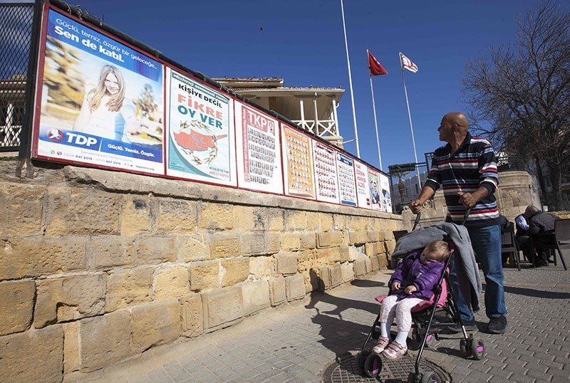 A man pushes a child in a push-cart past campaign posters for parliamentary elections in Nicosia, Turkish Republic of Northern Cyprus (TRNC), on Jan. 3, 2018. (AFP Photo)