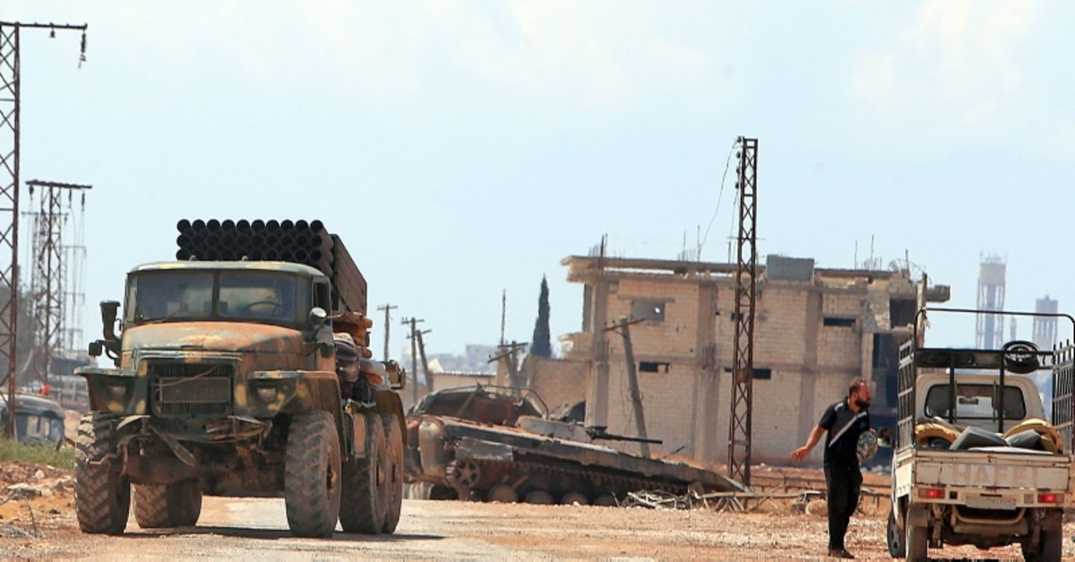 Syrian regime forces gather near the town of Khan Sheikhoun in the southern countryside of the opposition-held Idlib province on Aug. 18, 2019. (AFP Photo)