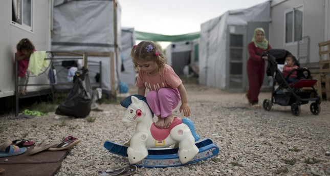 A Syrian child playing with a plastic toy horse at the Ritsona refugee camp about 86 kilometers north of Athens, May 25.