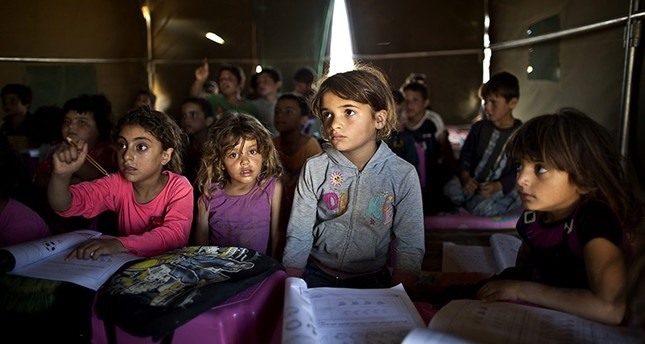 In this Tuesday, Aug. 11, 2015 file photo, Syrian refugee children attend a class at a makeshift school set up in a tent at an informal tented settlement near the Syrian border on the outskirts of Mafraq, Jordan. (AP Photo)