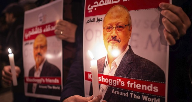 People hold posters of Saudi journalist Jamal Khashoggi and light candles during a gathering outside the Saudi Consulate in Istanbul, Oct. 25.