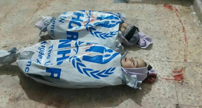 GRAPHIC IMAGEemThe bodies of two children wrapped in U.N. aid bags in eastern Ghouta./em