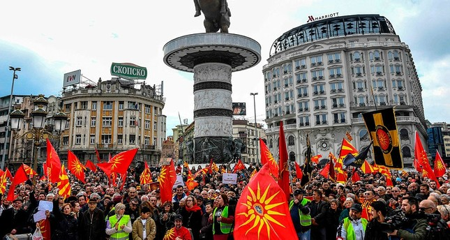 People wave Macedonian flags during a protest in a central square in Skopje on March 4, 2018. (AFP Photo)