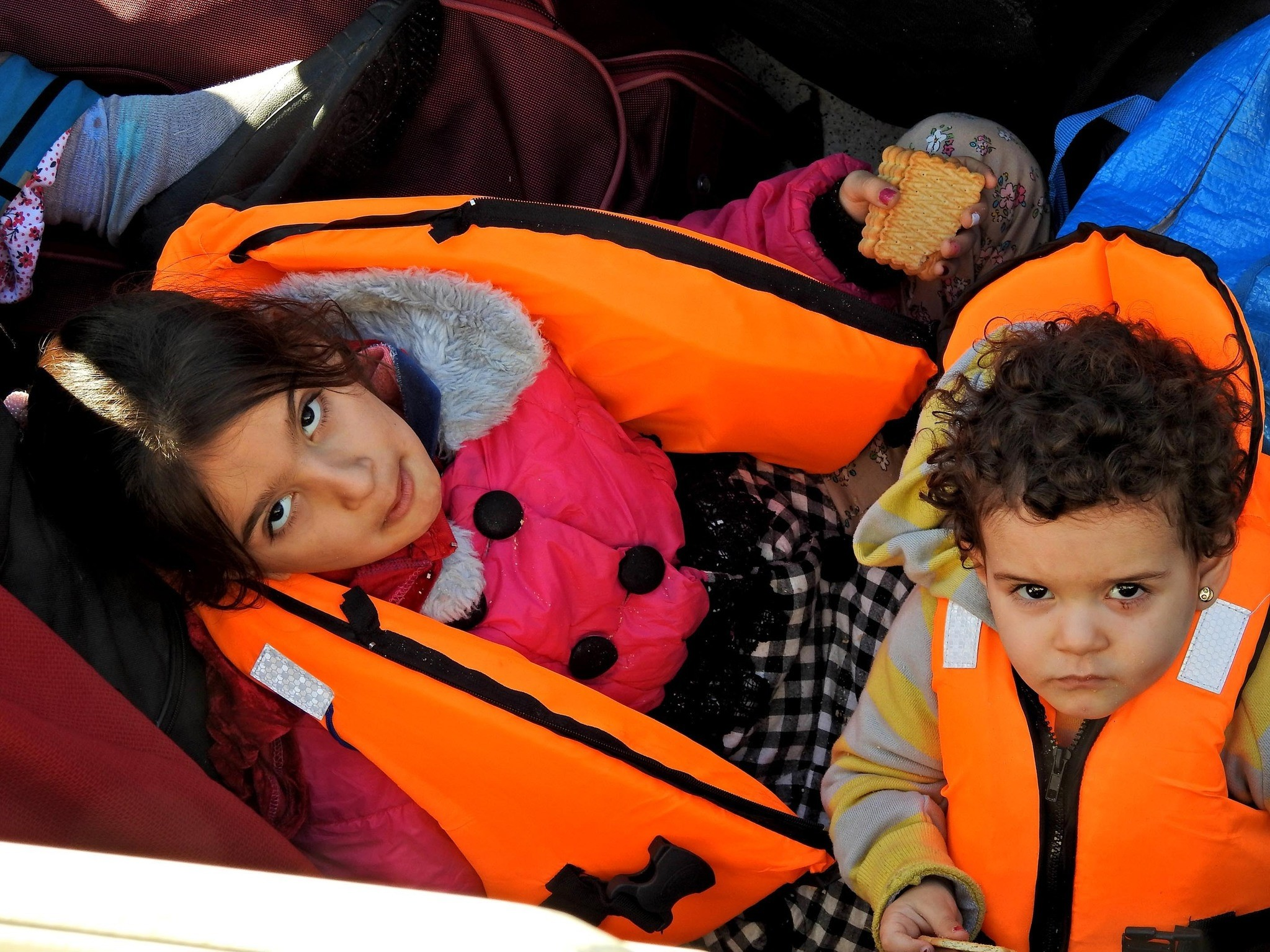 Two migrant children wait at the u00c7eu015fme port after they were brought there by the Coast Guard.