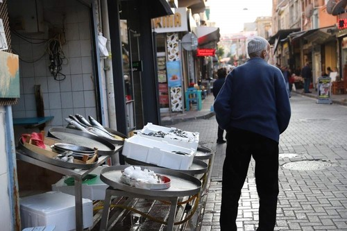 An elderly man stands next to a fish stall in Balat.