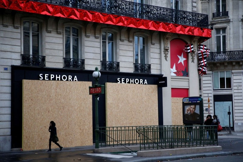 A woman walks past a closed shop protected by wood panels near the Opera district during a national day of protest by the ,yellow vests, movement in Paris, France, December 8, 2018. (Reuters Photo)