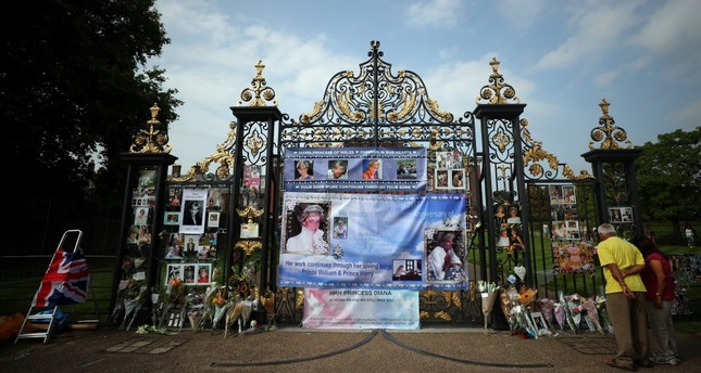 People leave flowers and tributes in memory of the late Princess Diana at the gates of her former residence Kensington Palace in London.