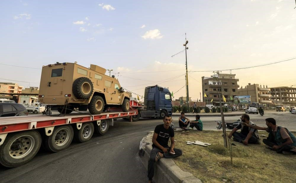 Military convoy carrying U.S.u2013made Oshkosh armoured vehicles, with flags bearing pictures of PKK leader Abdullah u00d6calan, en route to Raqqa for delivery to the YPG, passes through the Syrian city of Qamishli, Sept. 19.