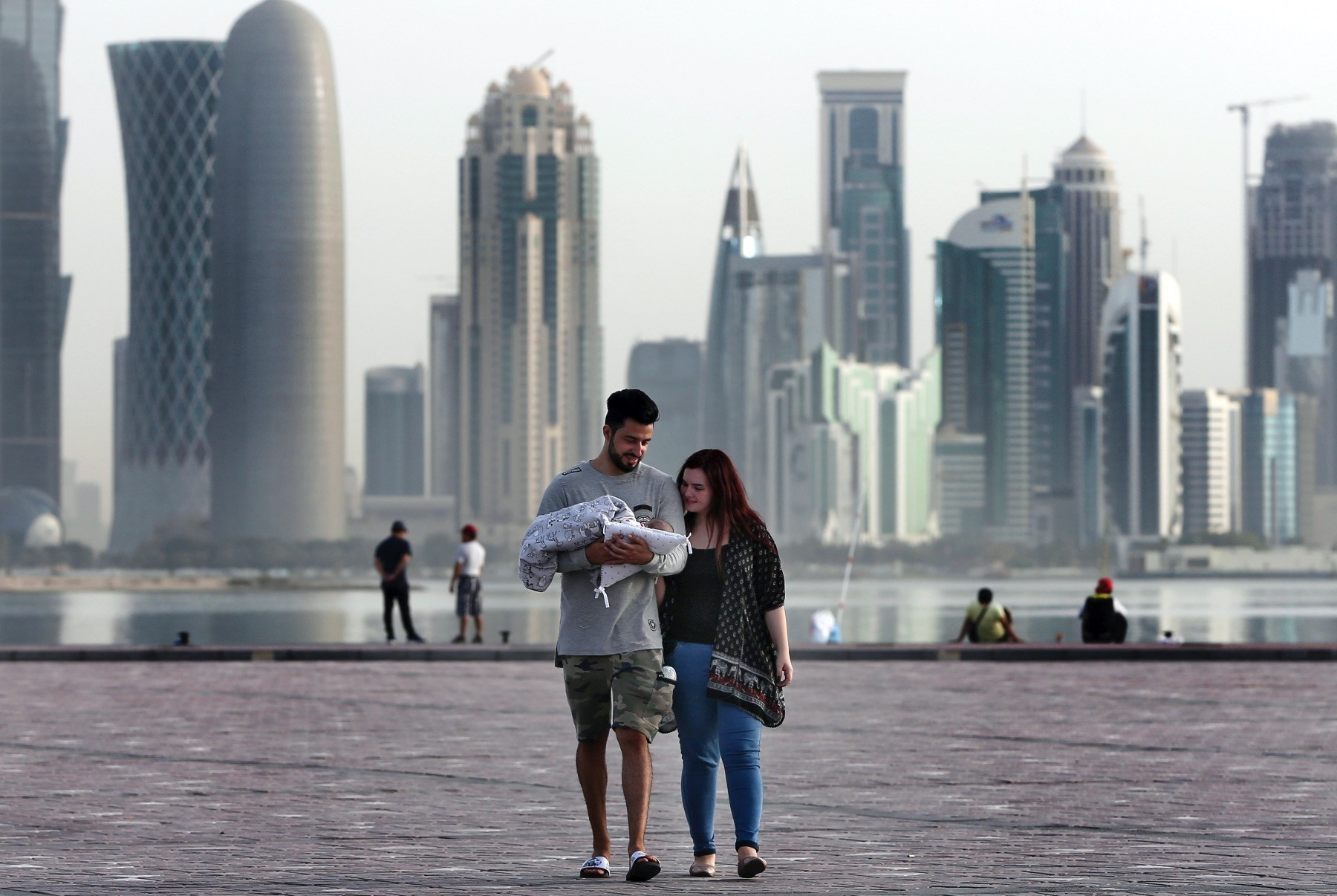 A couple takes a weekend walk with their newborn baby along the waterfront, Doha, Qatar, May 4.
