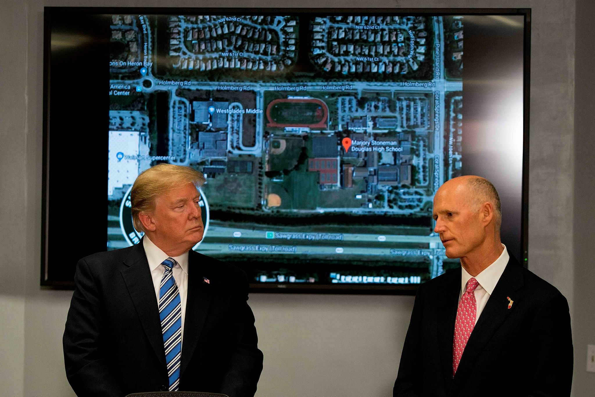 U.S. President Donald Trump (L) speaks with Florida governor Rick Scott while visiting first responders at Broward County Sheriffu2019s Office in Pompano Beach, FL, Feb.16.