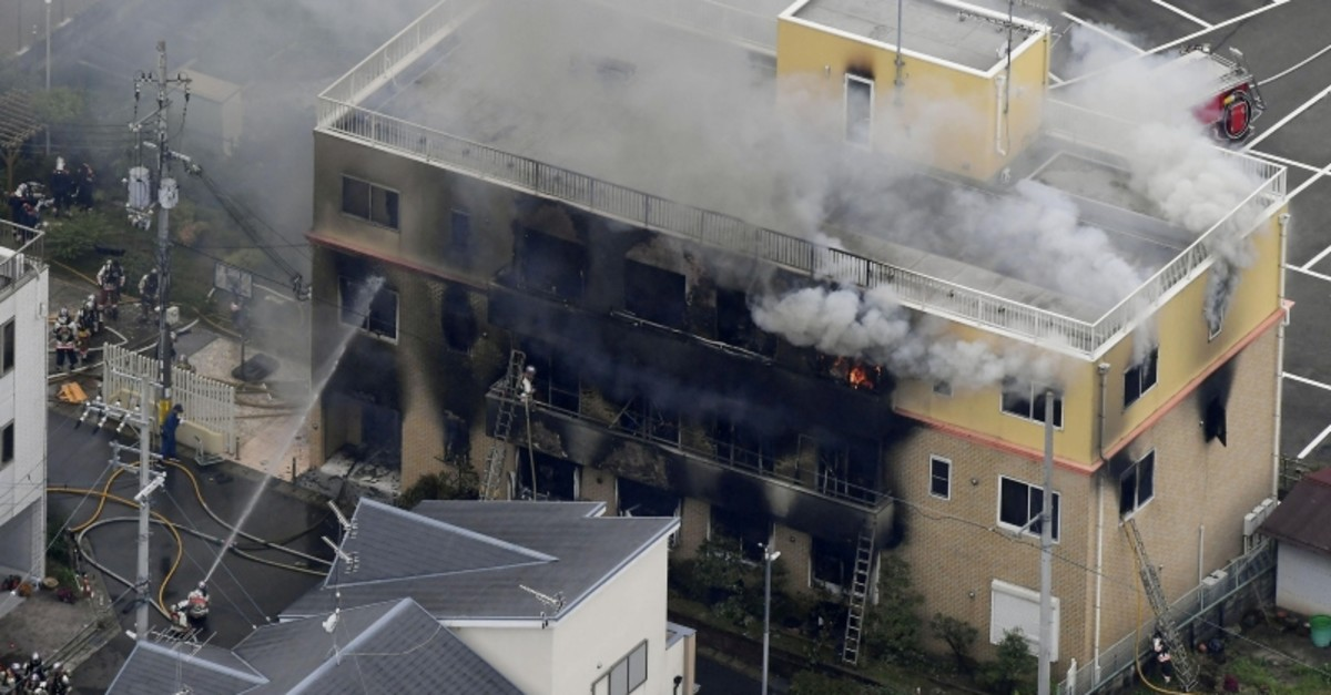 An aerial view shows firefighters battling fires at the site where a man started a fire after spraying a liquid at a three-story studio of Kyoto Animation Co. in Kyoto, Japan, July 18, 2019. (AP Photo)