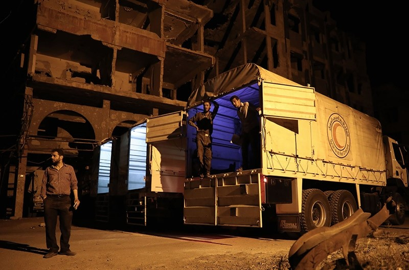 People prepare to unload supplies from a Syrian Arab Red Crescent (SARC) truck part of a SARC and UN aid convoy in the rebel-held town of Douma, on the eastern outskirts of Damascus, early on May 3, 2017. (AFP Photo)