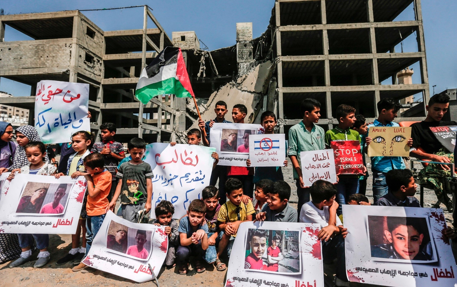 Palestinian children raise Palestinian flags in protest at a demonstration, Gaza City, July 15.