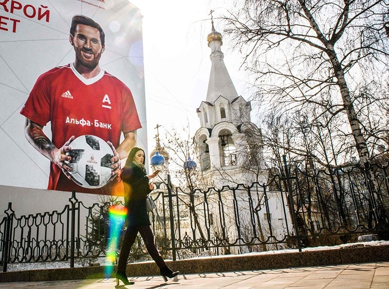 A woman walks past a wall painted with an advert for a local bank featuring Argentinian forward Lionel Messi ahead of the 2018 FIFA World Cup football tournament on April 4, 2018 in downtown Moscow. (AFP Photo)