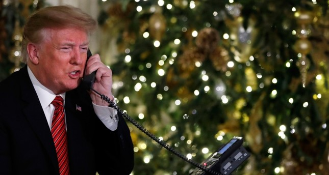 President Donald Trump speaks on the phone sharing updates to track Santa's movements from the North American Aerospace Defense Command NORAD Santa Tracker on Christmas Eve, Monday, Dec. 24, 2018. AP Photo