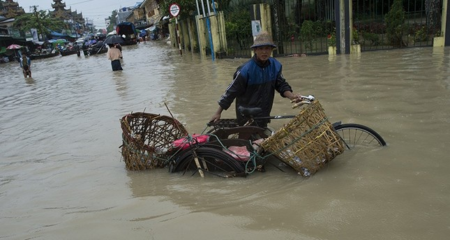 A man pushes his trishaw through the water after seasonal flooding hit the city of Pathein in the Irrawaddy region on August 13, 2016. AFP Photo