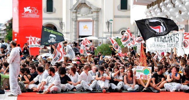 Climate and migration protesters, also to demanding an end to giant cruise ships being allowed to sail right up to the UNESCO city, occupy the red carpet of the 76th annual Venice International Film Festival, in Venice, Sept. 7 2019. (AP Photo)