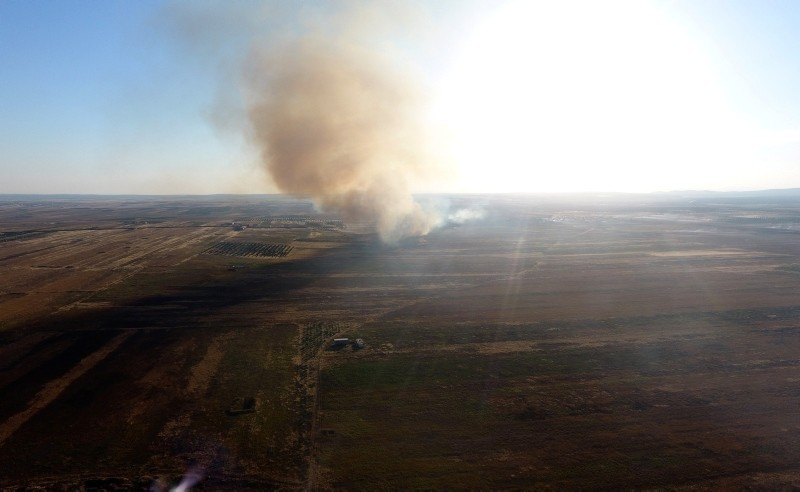 This drone footage captured by the Anadolu Agency on June 9, 2018, smoke rises from rural homes and fields surrounding the northwestern Syrian town of Tal Rifaat.