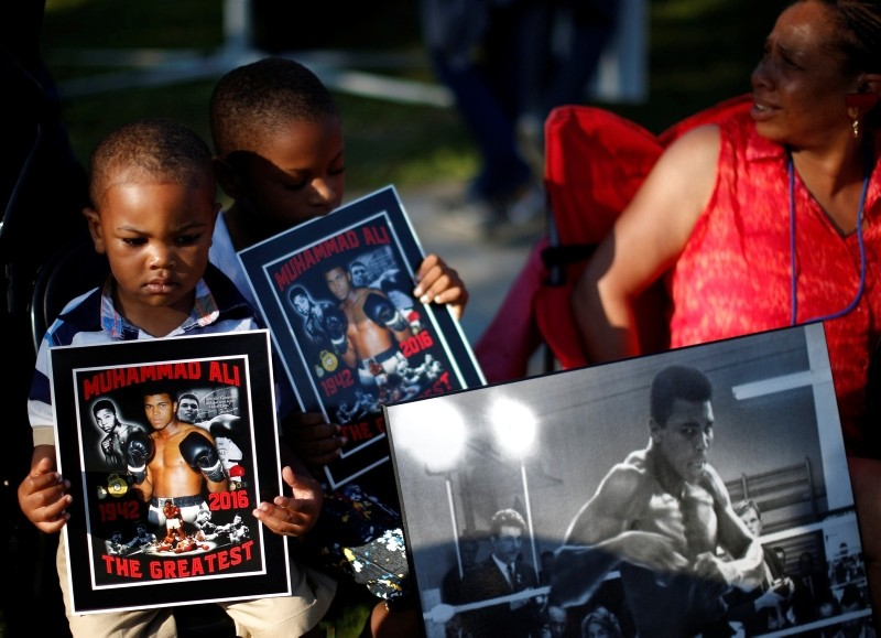 Brandon Liggons, 2, (L) holds an image of Muhammad Ali during the funeral procession for the three-time heavyweight boxing champion in Louisville, Kentucky, U.S., June 10, 2016. (Reuters Photo)