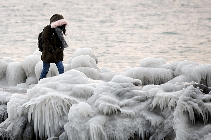 A woman walks on the pier that is covered with ice after few days of strong gusts of wind blowing waves of water over the bank of the lake of Geneva, in Geneva, Switzerland, Feb. 27, 2018. (EPA Photo)