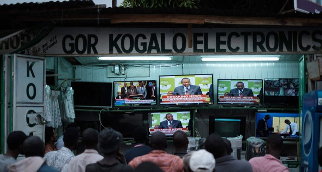 People watch live broadcast as Uhuru Kenyatta is declared the winner following presidential re-election results at a local electrical shop in Kisumu, on October 30, 2017. (AFP Photo)