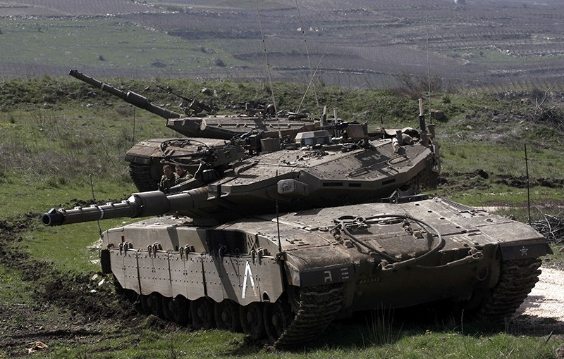 An Israeli tank is seen stationed near the village of Majdal Shams on the border with Syria, on March 19,2014 (AFP File Photo)