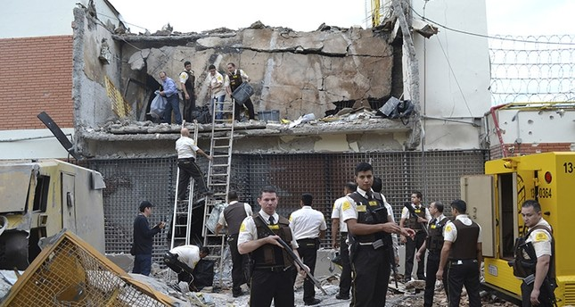 Guards and police inspect a vault that the assailants blew up early morning in Ciudad del Este, Paraguay, Monday, April 24, 2017. (AP Photo)