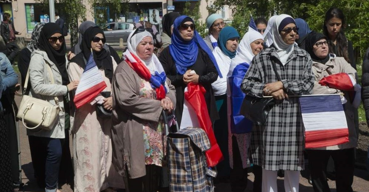 Women wearing headscarves hold French flags, Paris, May 16, 2014. (AP Photo)